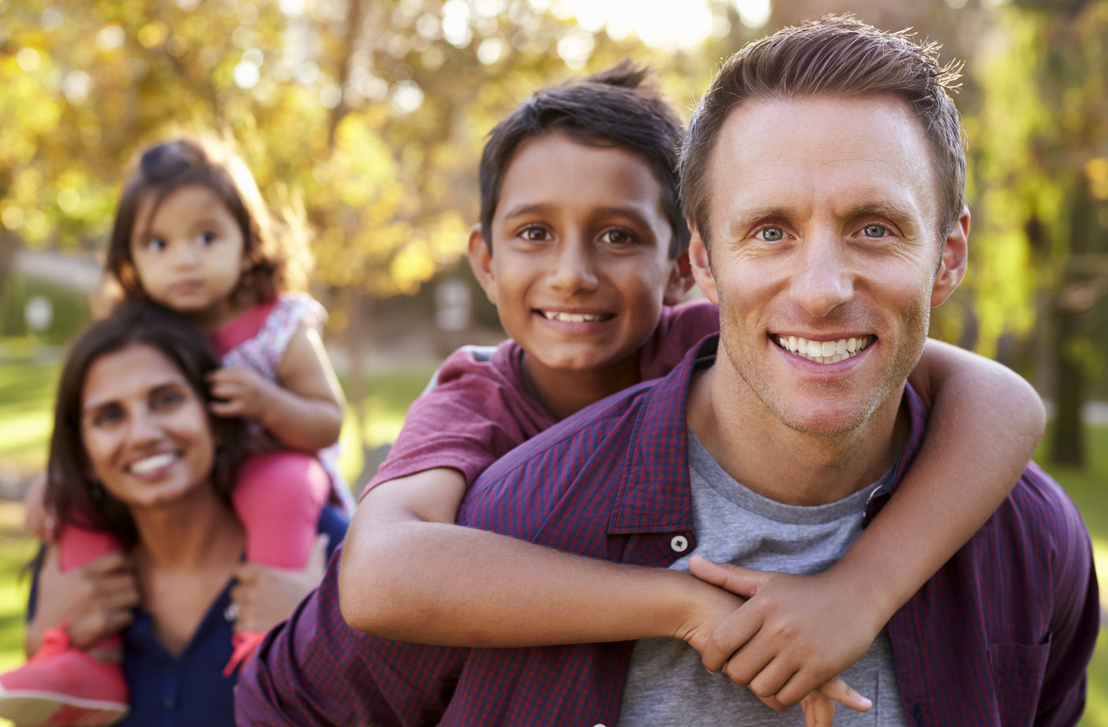 Home safety with Kidsafe Queensland - photo of mixed race family - Mum, Dad, son and daughter, playing in the backyard.